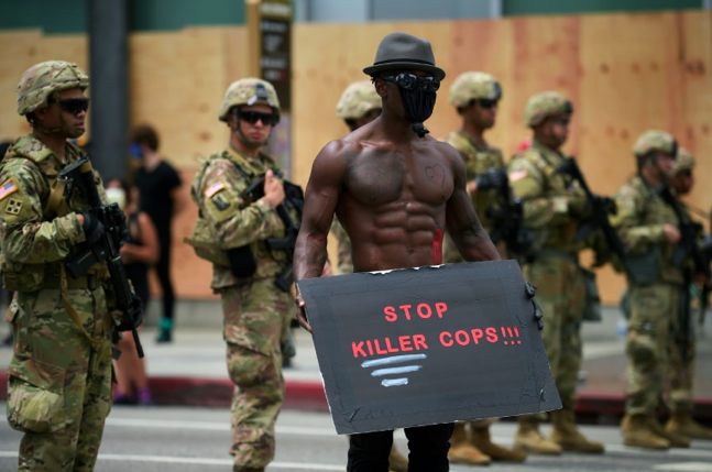 protester holds a placard in front of a row of Army National Guard during a demonstration over the death of George Floyd in Hollywood, California on June 2, 2020